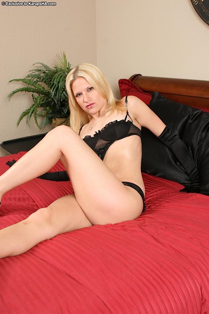 Блондинка с бритой киской Mia Faye снимает черное белье на красной кровати