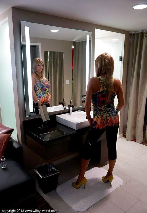 Сексуальная деваха с большими буферами встала перед зеркалом и оголяет свои интимные места