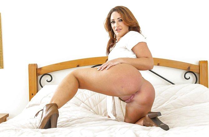 Пышная красивая женщина позирует голышом у кровати