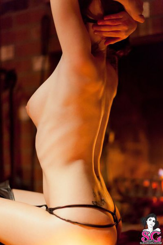 Роковая женщина позирует голышом с топором в руках