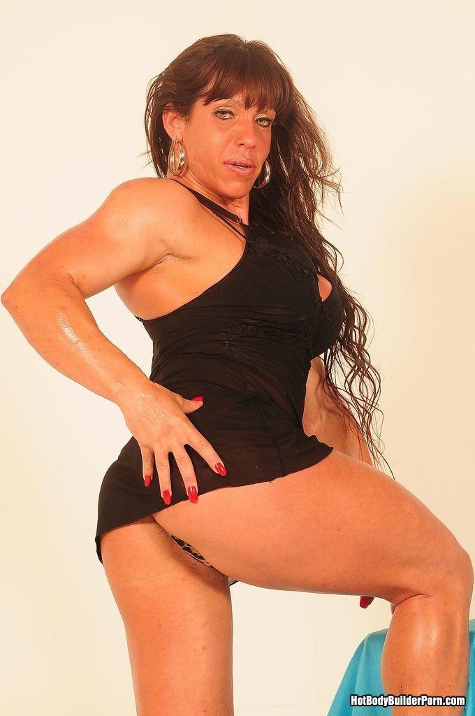 Женщина с бодибилдерским телом позирует перед камерой, а затем позволяет фотографу себя ласкать