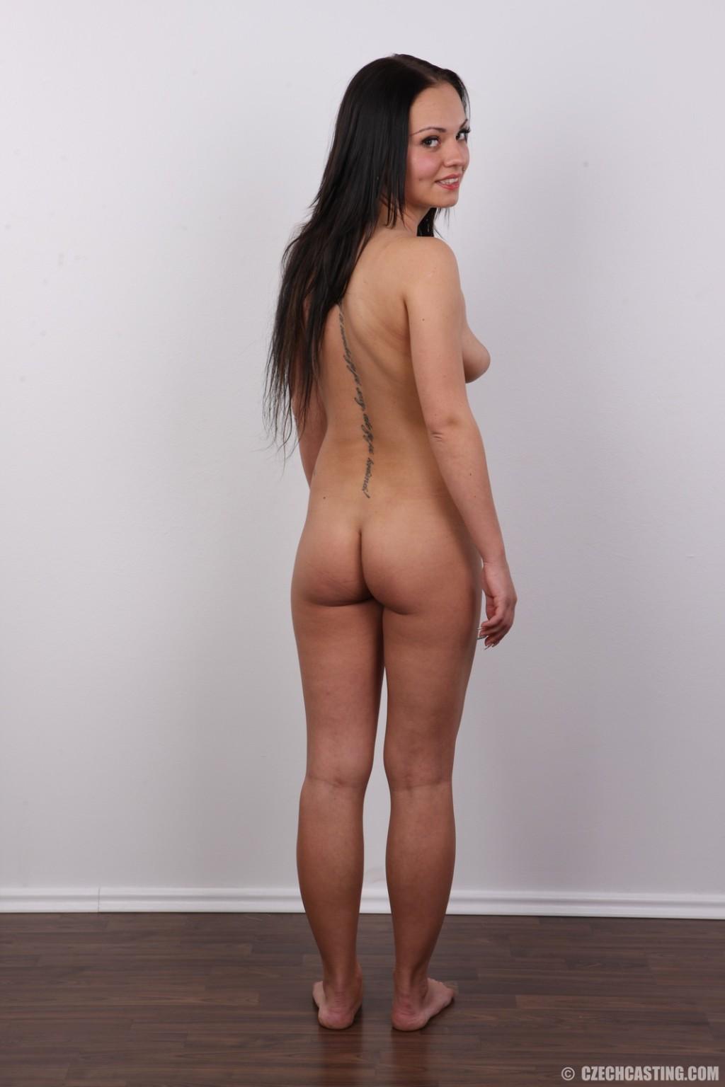 Брюнетка на кастинге в сексуальном белом белье улыбается на камеру