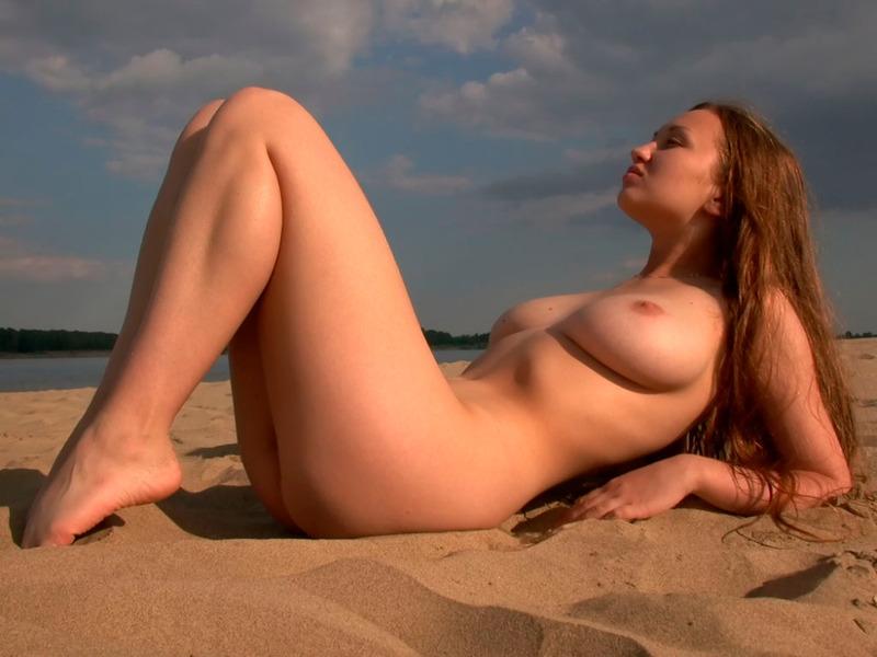 Кокетливая девушка купается в реке и греется на песочке