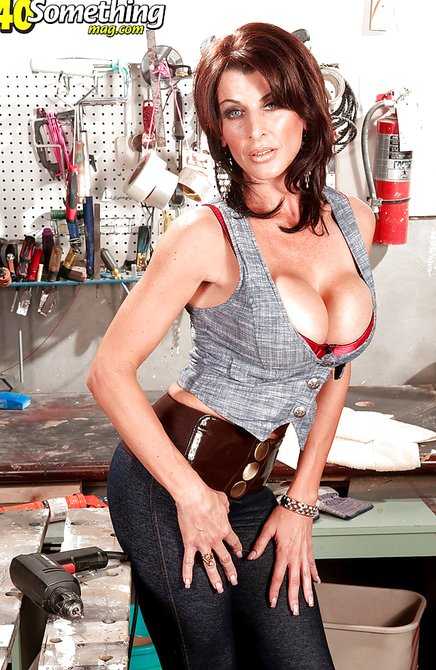 Сексуальная женщина с большими дойками позирует в гараже